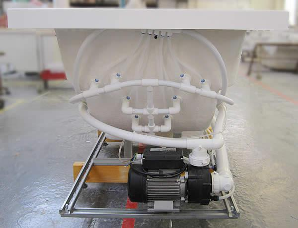 An end view of a hydrotherapy bath, showing the frame, pipework and pump.