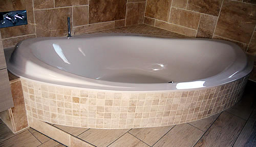 The bespoke double-ended bath in a tiled surround.