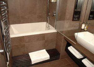 Small bathroom ideas - a deep soaking tub with overhead shower