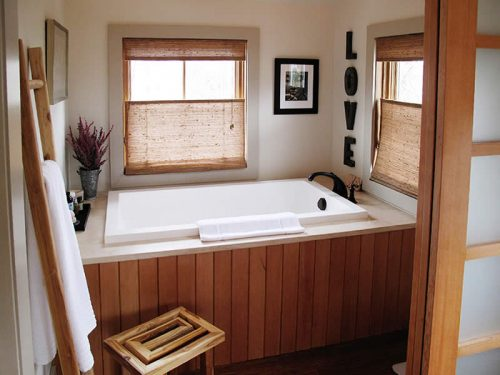 The Calyx deep soaking tub, shown inset with wooden panels and a marble deck