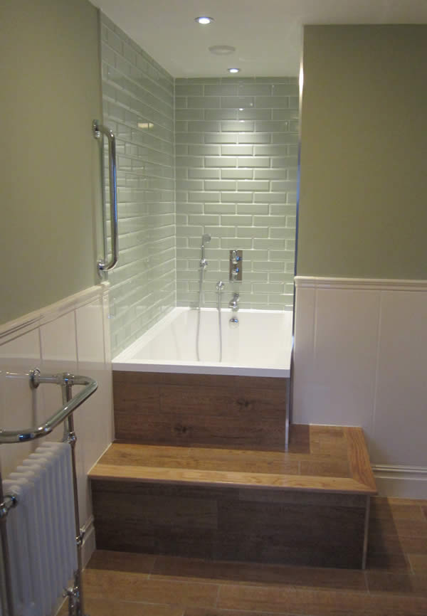 The Calyx soaking tub inset in awooden surround with built-in step