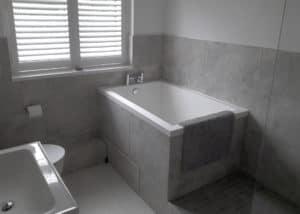 The Calyx soaking tub, set into a grey tiled surround.