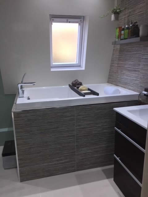 Nirvana corner bath, with tiled surround and external step.