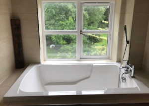 The Nirvana deep soaking tub, installed in a niche in the small en suite bathroom