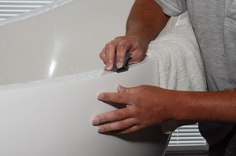 A worke hand finishing the rim of a Pleasance free standing bath.