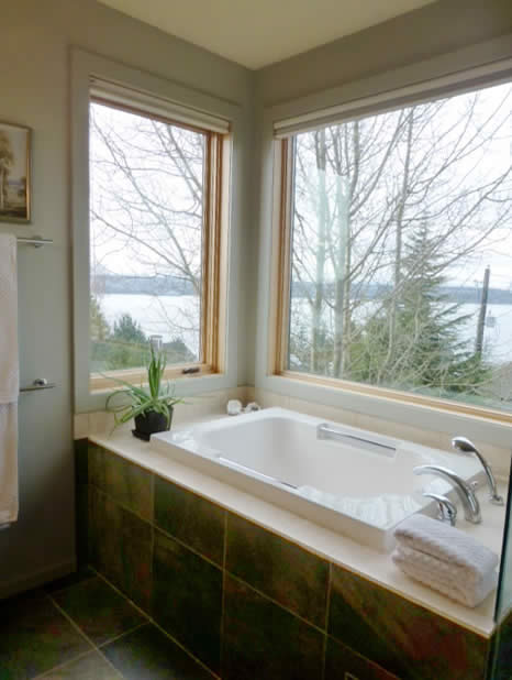 The traditionally styled Imersa deep soaking tub, set by a corner window