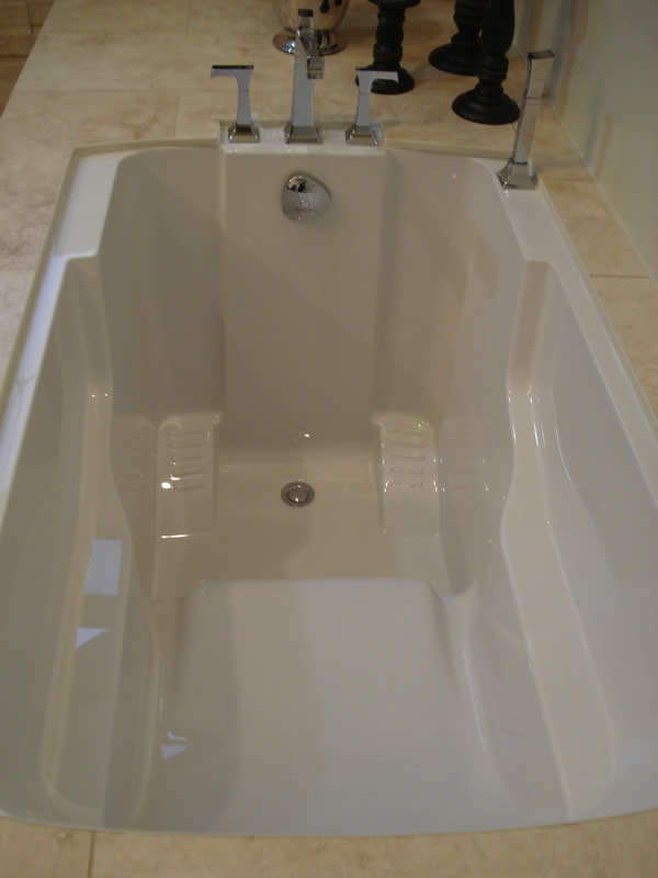 The Nirvana soaking tub's interior, showing its seat and supportive armrests.