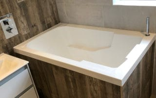 Nirvana deep soaking tub, corner installation, wood panel surround.
