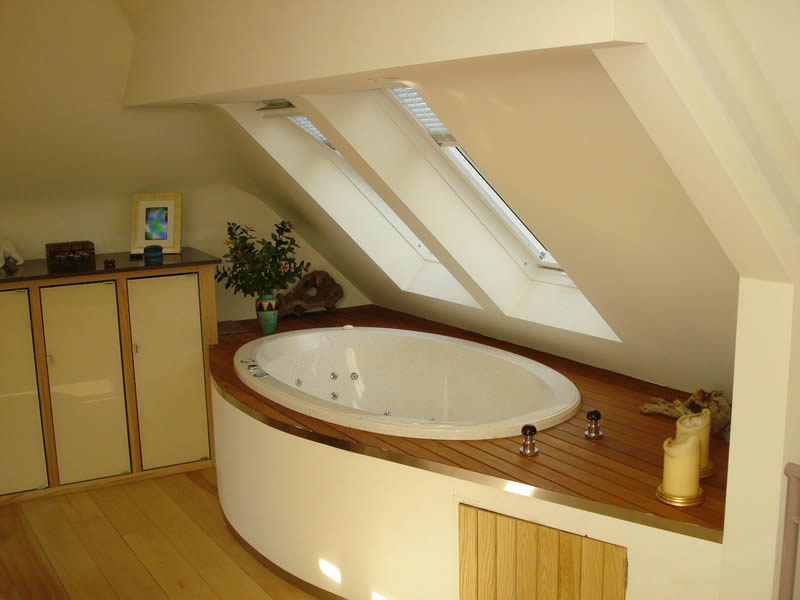 In this bathroom design, the bath is inset into an extended raised deck with storage.